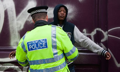 A young black man is searched by a Metropolitan police officer in London
